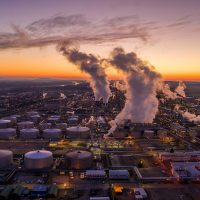 Drone point of view shot of an oil refinery under a moody sky at sunset.