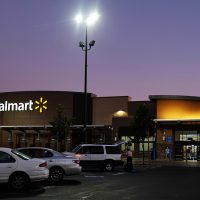 Folsom, California, USA - August 13, 2016: Approaching entrance of Walmart Superstore in Folsom, California, at twilight hour while customers are going in and out of the store.